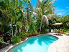 Secluded backyard with tropical folliage surrounding the pool